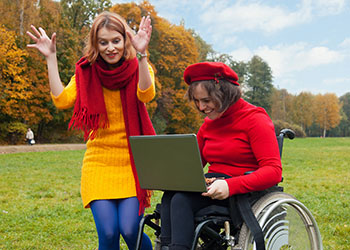 Two women wearing colorful clothing are outside in a field on a sunny autumn day. The woman on the left is gesturing with her hands, and the woman at the right is sitting in a wheelchair with a portable computer in her lap. She is looking at the screen.