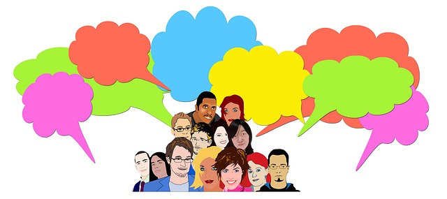 This cartoon-style image shows a group of about a dozen overlapping people, from the shoulders up. Arranged around them are colorful dialog balloons in the shape of clouds. The dialog balloons are empty.