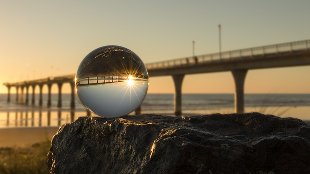 This dramatic image of a highway bridge at sunset has a crystal ball in the foreground. The bridge and the sunset are reflected upside down in the ball.